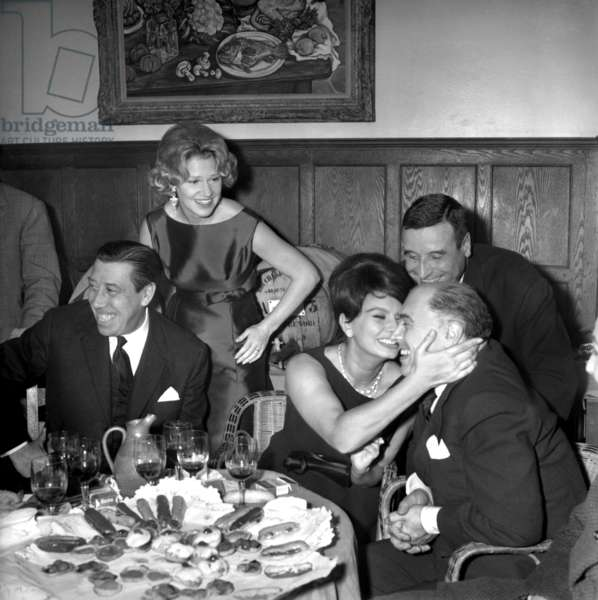 Fernandel, Sophia Loren, Carlo Ponti Under Look of Christian-Jaque and his Young Wife Laurence Cristol during Dinner For Wedding of Laurence Cristol November 26, 1961  (b/w photo)