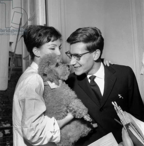 After Showing, Yves Saint Laurent Thanks Model Lucie Daouphars, Called Lucky, Who Presents Him The Toy Poodle of A Rich American Client on July 31, 1958 (b/w photo)