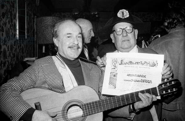 French Dress Designer Jacques Esterel Playing Guitar, February 8, 1974 (He'S Happy Because He Has Been Designated As Ambassador of The Republic of Montmartre, Paris), He'S With Pommard, Local Policeman of The Old Montmartre (b/w photo)