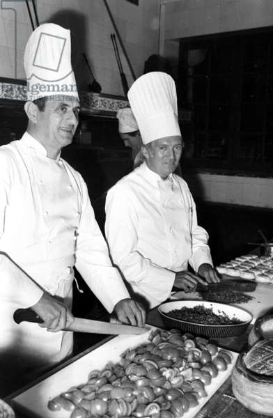 Paul Bocuse and pastry cook Gaston Lenotre preparing a meal at Breteuil castle, France, 1975 (photo)