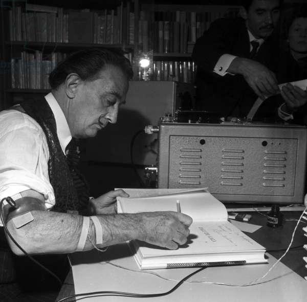 "Spanish painter Salvador Dali signing the book ""Dali de Gala"" written by Robert Descharnes, Paris, 10 December 1962 (photo)"