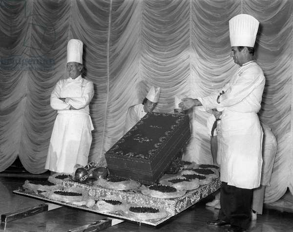 French pastry cook Gaston Lenotre and French cook Paul Bocuse presenting their creation at a party organized by Cartier, Paris, 1983 (b/w photo)