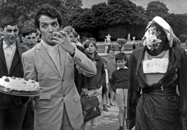 French Writer Alexandre Kalda With A Custard Tart Near A Dummy Representing The Prince of Baroda, June 24, 1966 (b/w photo)
