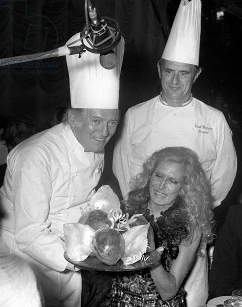 French pastry cook Gaston Lenotre and French cook Paul Bocuse presenting their creation to Dalida, Paris, 1983 (b/w photo)