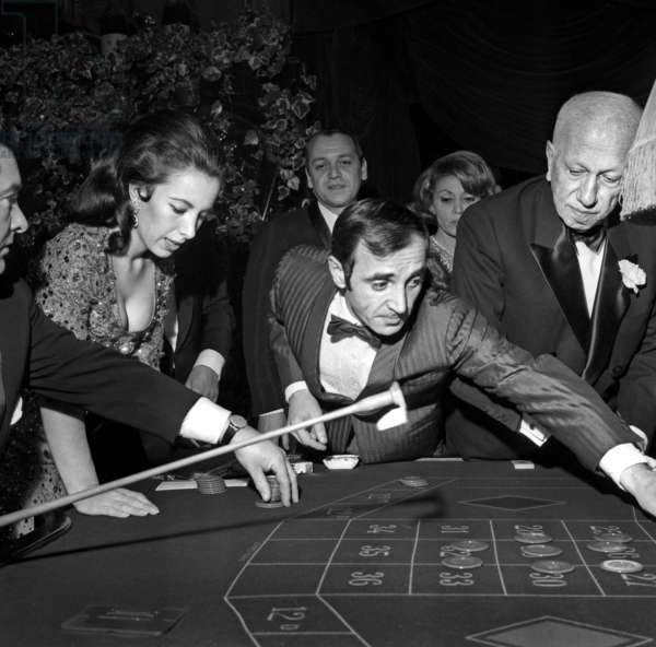 Charles Aznavour playing roulette at the Charity Gala organized by Maurice Chevalier, Maxim's Restaurant, Paris, 27 January 1965 (photo)