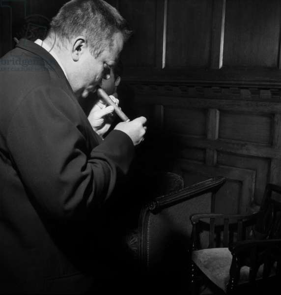 """Orson Welles, lighting a cigar, at the presentation of the film """"The Trial"""", Paris, 23 March 1962 (photo)"""