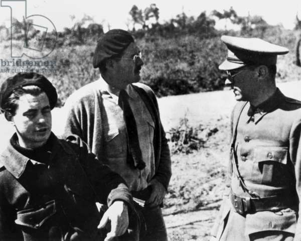 Ernest Hemingway (1899-1961) with Gustav Regler and Joris Ivens in uniform during Spanish civil war filming of Terre d' Espane 1937