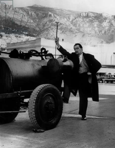Salvador Dali posing near a tarring machine in Monaco on April 23, 1959. He's going to make a tar scale model of a cathedral in Arizona desert