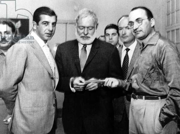American writer Ernest Hemingway (1899-1961) giving a check to Emilio Romero, director of Spanish Pueblo's publishing firm, here with torero Antonio Ordonez (left) in Madrid August 20, 1960