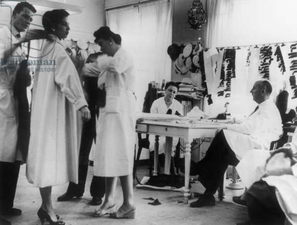 French dress designer Christian Dior (1905-1957), with a white shirt, in his workshop when he attend to a fitting, early 50's