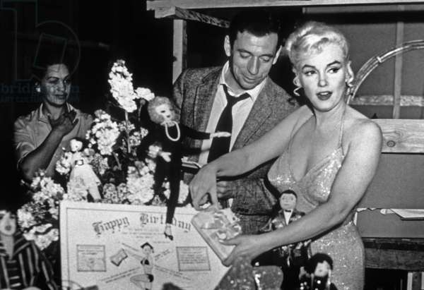 French Actor Yves Montand, American Actress Marilyn Monroe and a birthday cake.