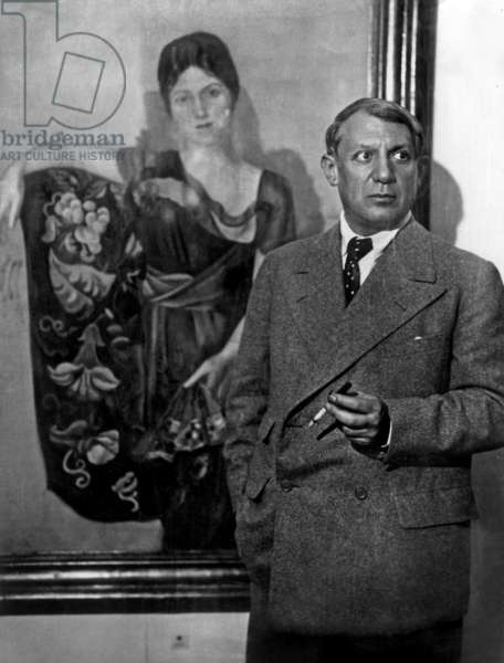 Painter Pablo Picasso in front of the portrait of Olga during exhibition in Paris, 1931 (b/w photo)