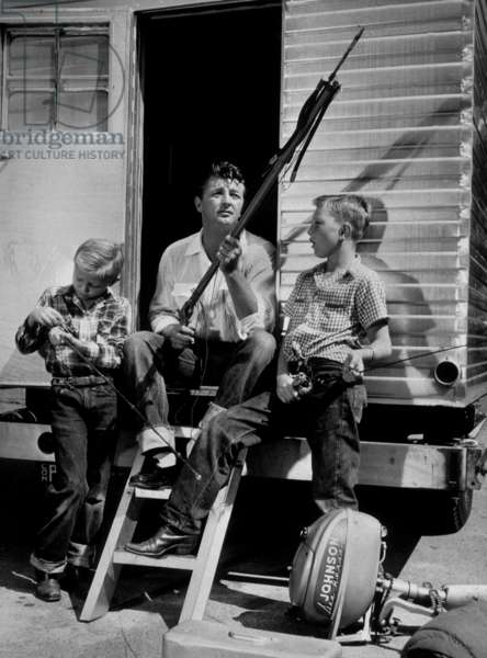 Robert Mitchum with his two children Jim and Chris preparing a game of fishing in 1952