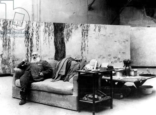 French painter Claude Monet (1840-1926) in his workshop in front of one of his paintings Waterlilies c. 1918