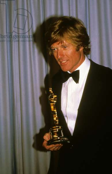 Robert Redford holding his Best Director academy award for his movie