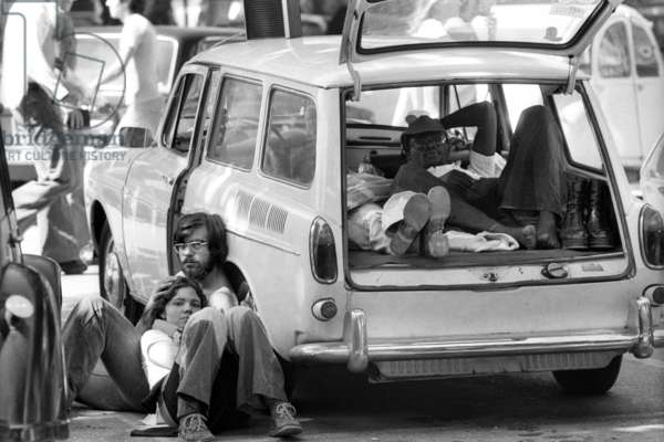 Music festival in Orange : young people resting on a parking. France, 1975.