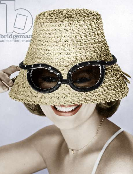 Woman with a big straw hat putting her sunglasses on the hat colourized document