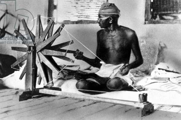 Mahatma Mohandas Karamchand Gandhi (1869-1948) Indian religious man and politician, spinning sitting cross-legged, c. 1925