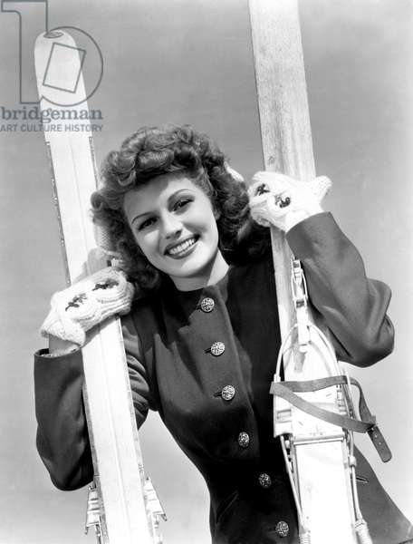 Rita Hayworth ready for winter, poses with her skiis, c. 1951