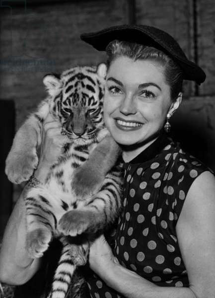 "Esther Williams with a young tiger named ""Esther"" six week old, which she adopted during her visit to the London Zoo on September 6, 1956"