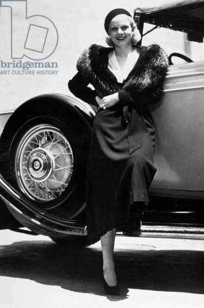 American Actress Jean Harlow (1911-1937) posing near a car