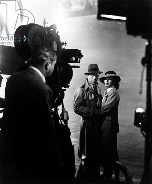 Michael Curtiz directed Humphrey Bogart (impermeable Burberry and Fedora hat) and Ingrid Bergman on the filming of Casablanca in 1942.