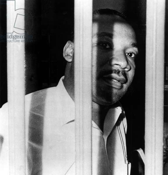 MARTIN LUTHER KING, JR, peers between the bars of his jail cell in the St. John's County Jail, Florida. He was arrested for trespassing, during an integration demonstration, 6/11/62