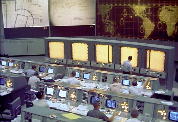 A global view of the Mission Command Centre (MCC) in Houston, Texas, during the flight of the American Space Mission Gemini 5, August 21, 1965. Note the screen on the front of the MCC that is used to track the progress of the Gemini spacecraft