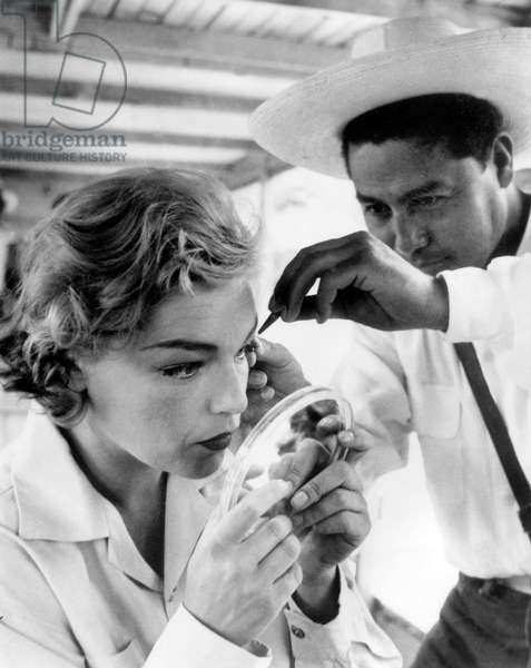 Actress Simone Signoret putting some make-up on, looking in a mirror on set of film 'La Mort Au Jardin', May 20, 1956 (b/w photo)