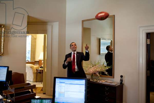 President Barack Obama plays with a football in the Outer Oval Office March 4, 2009