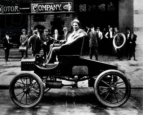 Henry Ford posing in front of his factory in one of his first cars 1907- Henry Ford driving one of his car 1907 outside his factory