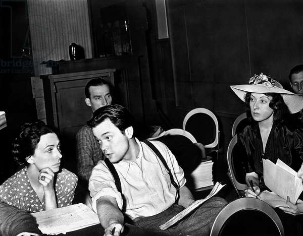 American Actor, writer, producer and director Orson Welles talking with Agnes Moorehead on a theatre stage with members of the Mercury Theatre 1938