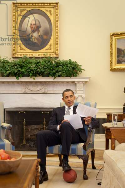 President Barack Obama rests his foot on a football during the Domestic Policy Council Meeting in the Oval Office March 25, 2009