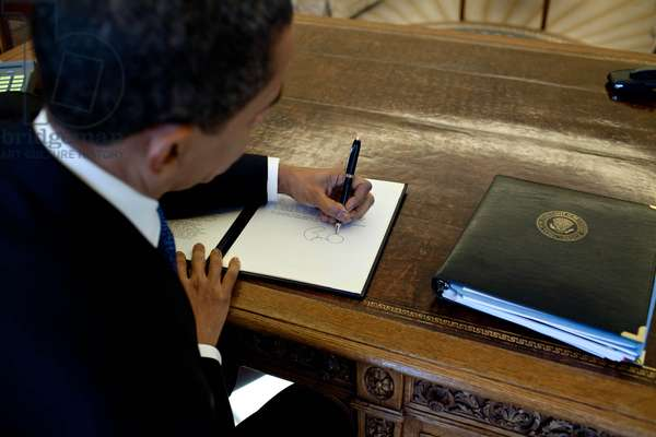 President Barack Obama writes at his desk in the Oval Office March 3, 2009