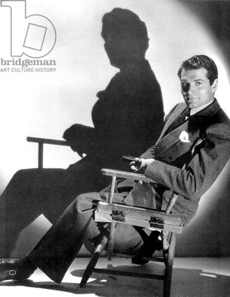 English Actor Laurence Olivier (1907-1989) seated on a chair's director c. 1939