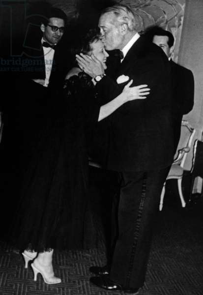 French Singer Edith Piaf (1915-1963) kissed by Maurice Chevalier during a party at Broadway Theatre in New York October 29, 1955