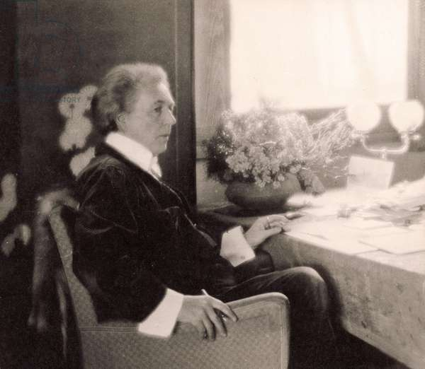 American architect Frank Lloyd Wright (1867-1959) at home in Taliesin, with papers spread before him on a table. 1924