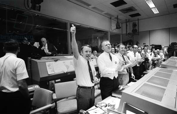 """Johnson Space Center, April 17, 1970 : Three of the four Apollo 13 Flight Directors applaud the successful splashdown of the Command Module """"Odyssey"""" while Dr. Robert R. Gilruth, Director, Manned Spacecraft Center (MSC), and Dr. Christopher C. Kraft Jr., MSC Deputy Director, light up cigars (upper left). The Flight Directors are from left to right: Gerald D. Griffin, Eugene F. Kranz and Glynn S. Lunney"""