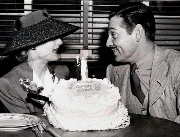 Clark Gable et Carole Carol Lombard first Wedding Aniversary Hollywood in Gable's dressing room at MGM Married March 29, 1939 in Kingsman Arizona Gable satisfied with the anniversary cake le 30 mars 1940 couple de maries se regardant gateau du premier anniversaire fashionable hat
