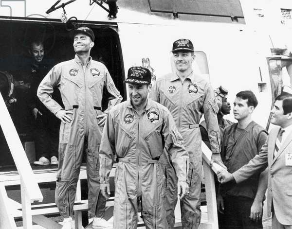 The crew of the Apollo 13 mission step aboard the U.S.S. IwoJima, prime recovery ship for the mission, following splashdown and recovery operations in the South Pacific on April 17, 1970 : Fred. W. Haise, Jr., lunar module pilot; James A. Lovell Jr., commander; and John L. Swigert Jr., command module pilot