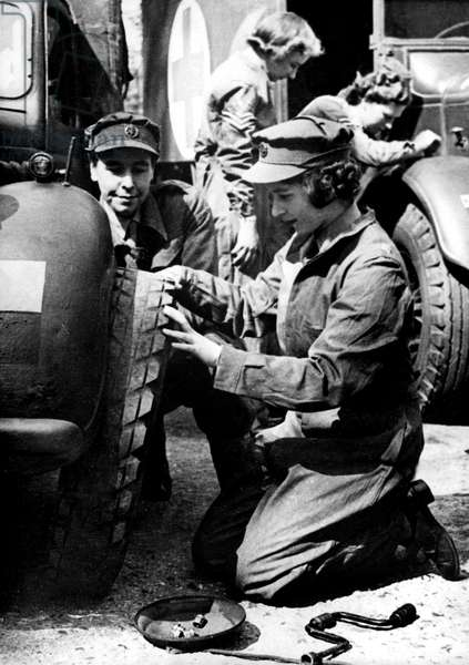 Young princess Elizabeth, future Queen Elizabeth II, learning how to change a wheel in training camp during the war, c.1945 (b/w photo)