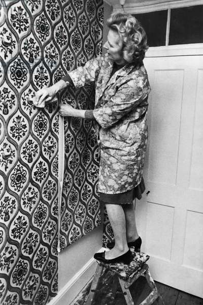 Margaret Thatcher hanging wallpaper at her country home at Scotney Castle, 23 October 1975 (b/w photo)