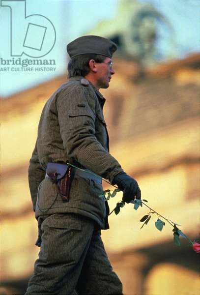German Soldier With A Flower at Fall of Berlin Wall in November 1989 (photo)