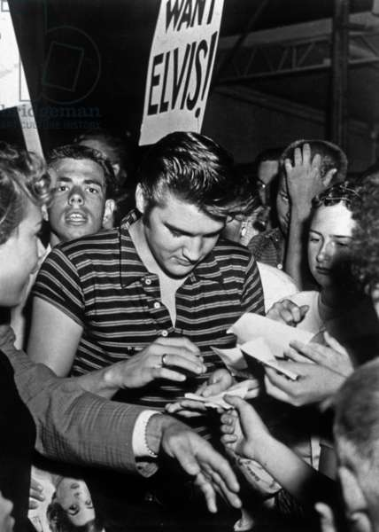 Elvis Presley signe des autographes à ses admirateurs en 1956 (photo b/w)