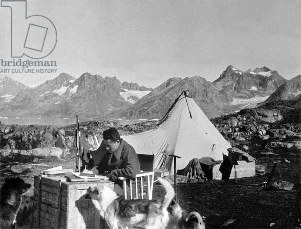 Paul Emile Victor working in front of his tent, fjord of Kangerdlugssuatsiak, Greenland, Summer, 1936 (b/w photo)