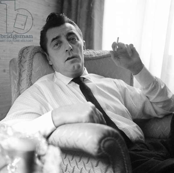 Robert Mitchum relaxing in this London flat, London, UK, 1960 (b/w photo)