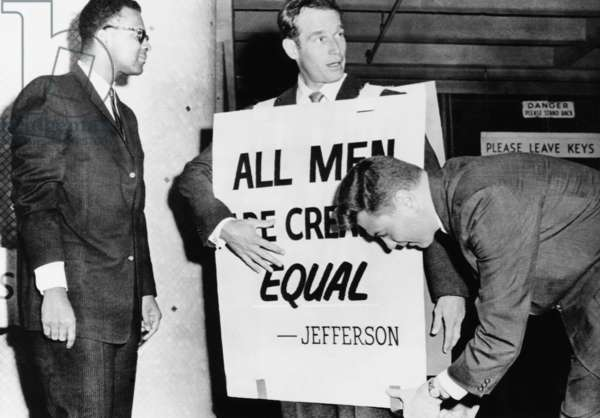 Actor Charlton Heston adjusts a sandwich board for a civil rights demonstration. Oklahoma City, May 27, 1961. His sign reads, 'All Men are Created Equal.'