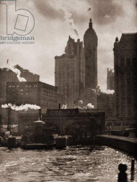 THE CITY OF AMBITION (1910), by Alfred Stieglitz, is a soft focus, pictorialist image of the New York City waterfront and skyscrapers. Photogravure from CAMERA WORK, no. 36, 1911
