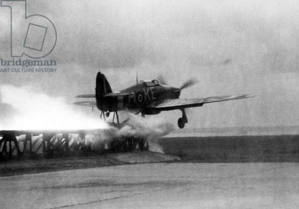 A Royal Air Force Hawker Hurricane is catapulted down a launching ramp on the bow of a merchant ship. These aircraft, used to patrol convoys while at sea, were ditched in the sea when they ran out of fuel and later hoisted back on board the ship. World war Two 1945 (b/w photo)