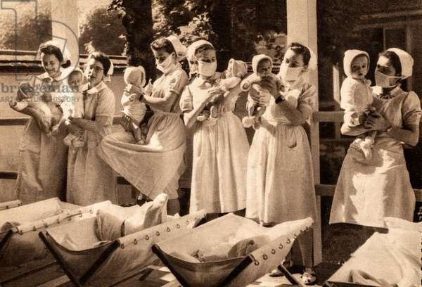 Masked Nurses Attend to Infants at Hospital Saint-Michel, Paris, Paris, France, c.1935 (postcard)